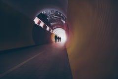 siluetas Lente-señaladas por medio de luces de la gente en un túnel circular para los peatones y los ciclistas Imágenes de archivo libres de regalías