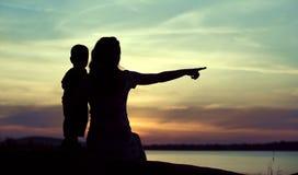Siluetas oscuras de la madre con el niño Fotos de archivo libres de regalías