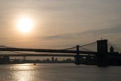 Siluetas oscuras de secciones de los puentes de Brooklyn, de Manhattan y de Willamsburg con el sol bajo en el horizonte Fotos de archivo