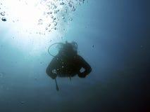 Siluetas subacuáticas del buceador contra el sol Fotografía de archivo