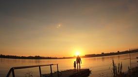 Siluetas, un pequeño niño y mujer que se colocan en el embarcadero por el agua en la puesta del sol almacen de metraje de vídeo