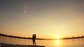 Siluetas, un pequeño niño y mujer que se colocan en el embarcadero por el agua en la puesta del sol metrajes