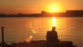 Siluetas, un pequeño niño y mujer que se sientan en el embarcadero por el agua en la puesta del sol almacen de video