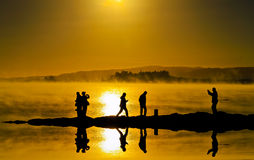 Siluetas y reflejo en la superficie del agua de la gente Foto de archivo