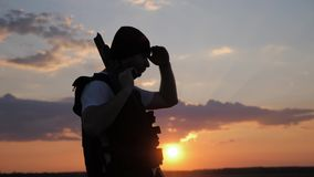 Siluetea al soldado con el arma contra una puesta del sol almacen de metraje de vídeo