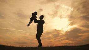 Siluetea el padre y al pequeño hijo que juegan en el prado en el tiempo de la puesta del sol Concepto de familia amistosa almacen de video