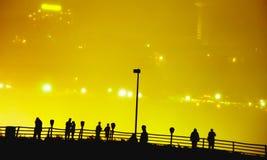 Siluetea a gente del od en el observatorio de Niagara Falls en la noche del lado americano con el lado canadiense iluminado a tra Imagen de archivo libre de regalías