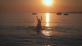 Siluetea a la madre y la hija se sienta en la playa en la puesta del sol Concepto de familia amistosa, forma de vida metrajes
