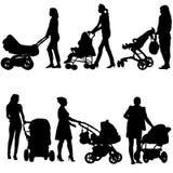 Siluetea a madres de los walkings con los cochecitos de bebé Foto de archivo
