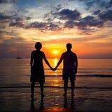 Siluetea pares jovenes en la playa en la puesta del sol Fotos de archivo libres de regalías