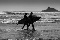 Siluetea a personas que practica surf Fotos de archivo