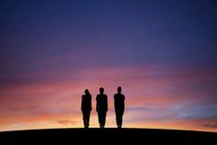 Silueteado tres adolescentes que se colocan derecho en puesta del sol Fotografía de archivo libre de regalías