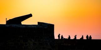 Siluetean un canon y a una gente antiguos en una pared a de la fortaleza Imagen de archivo libre de regalías