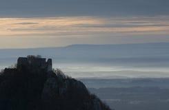 Silueted Schlossruine gegen einen Sonnenaufganghimmel Stockbilder