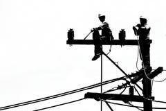 Electricista de la silueta que trabaja en el poste de la electricidad Imagen de archivo