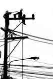 Electricista de la silueta que trabaja en el poste de la electricidad Fotografía de archivo libre de regalías