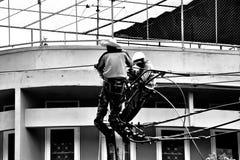 Electricista de la silueta que trabaja en el poste de la electricidad Fotos de archivo libres de regalías