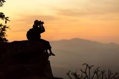 Siluetee al fotógrafo de la muchacha que se sienta en las rocas en el alto shooti Fotos de archivo libres de regalías