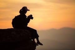 Siluetee al fotógrafo de la muchacha que se sienta en las rocas en el alto shooti Foto de archivo