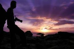 Siluetee al fotógrafo que defiende en las rocas el mar Imagen de archivo