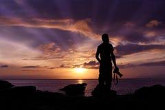 Siluetee al fotógrafo que defiende en las rocas el mar Foto de archivo