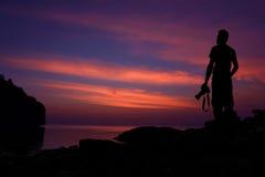Siluetee al fotógrafo que defiende en las rocas el mar Foto de archivo libre de regalías