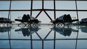 Siluetee al grupo de pasajero que camina con equipaje en el aeropuerto almacen de metraje de vídeo