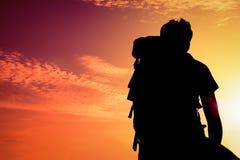 siluetee al hombre con el bolso para mirar para arriba el sol imagen de archivo libre de regalías