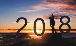 Siluetee al hombre de la libertad que se coloca en la roca, aumentando la mano para arriba bajo puesta del sol 2018 Años Nuevos q Imagen de archivo libre de regalías