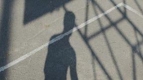 Siluetee al hombre de salto de la sombra que lanza la bola al aro, entrenamiento del baloncesto almacen de metraje de vídeo