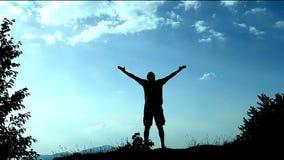 Siluetee al hombre joven que permanece encima de la montaña y de levantamientos sus manos como muestra del logro, del éxito y de  metrajes