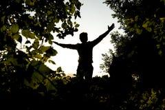 Siluetee al hombre joven que se abre los brazos en el campo Imagen de archivo