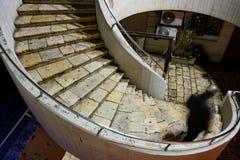 Siluetee al hombre que desciende la caja al aire libre curvada de la escalera - luz de calle Imagenes de archivo