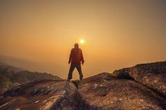 Siluetee al hombre que se coloca en el cielo de la puesta del sol Foto de archivo libre de regalías
