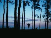 Siluetee al hombre que se coloca en manos de levantamiento del bosque con el fondo de la puesta del sol del mar Fotos de archivo