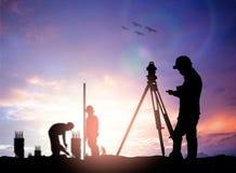 Siluetee al ingeniero de la encuesta que trabaja en un solar sobre la falta de definición Fotos de archivo libres de regalías