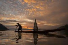 Siluetee al pescador del lago Bangpra en la acción al pescar Fotos de archivo