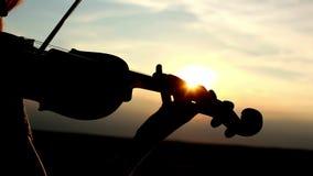Siluetee al violinista de la muchacha que toca el violín en el fondo del cielo de la puesta del sol almacen de video