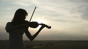 Siluetee al violinista de la muchacha que toca el violín en el fondo del cielo de la puesta del sol almacen de metraje de vídeo
