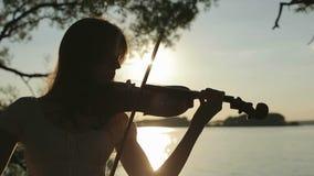 Siluetee al violinista de la muchacha que toca el violín en la puesta del sol en el lago almacen de metraje de vídeo