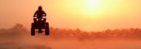 Siluetee ATV o las bicis del patio saltan en puesta del sol fotos de archivo libres de regalías
