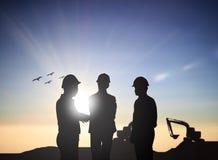 Siluetee del ingeniero trasero de tres el negocio que habla personas en un bui Foto de archivo libre de regalías