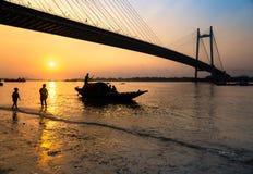 Siluetee el barco en la puesta del sol en el río Hooghly con el puente del setu de Vidyasagar en el contexto Foto de archivo