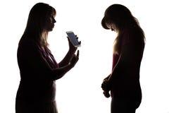 Siluetee el conflicto de los padres y de los niños adolescentes debido al entretenimiento electrónico Foto de archivo