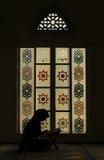 Siluetee el Corán musulmán de la lectura de la mujer por la tarde en la mezquita Imágenes de archivo libres de regalías