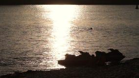 Siluetee el esquí del jet en la costa en puesta del sol amarilla almacen de metraje de vídeo