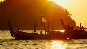 Silhouette group of long tail boat convertedfloating in the andaman sea with golden light Stock Footage