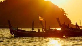 Siluetee el grupo de barco de la cola larga convertedfloating en el mar de andaman con la luz de oro metrajes