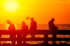 Siluetee el grupo de la sombra de amistad adolescente en la costa de mar Foto de archivo libre de regalías