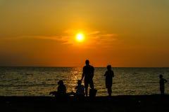 siluetee el juego de la gente con el perro dos en puesta del sol de la playa Fotografía de archivo